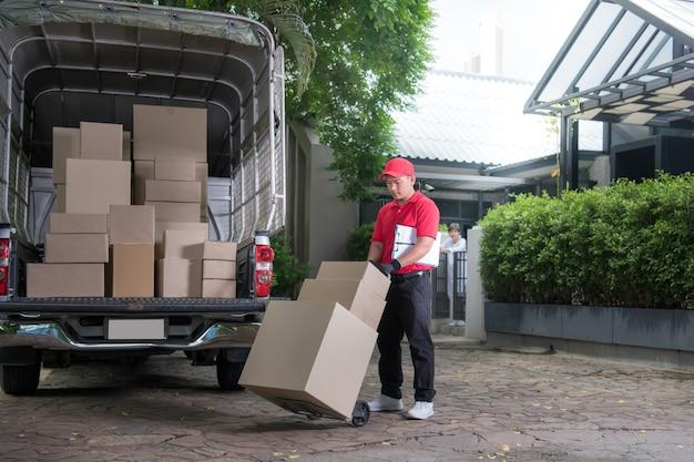 Livreur asiatique en uniforme rouge la livraison de boîtes à colis à la femme destinataire à la maison