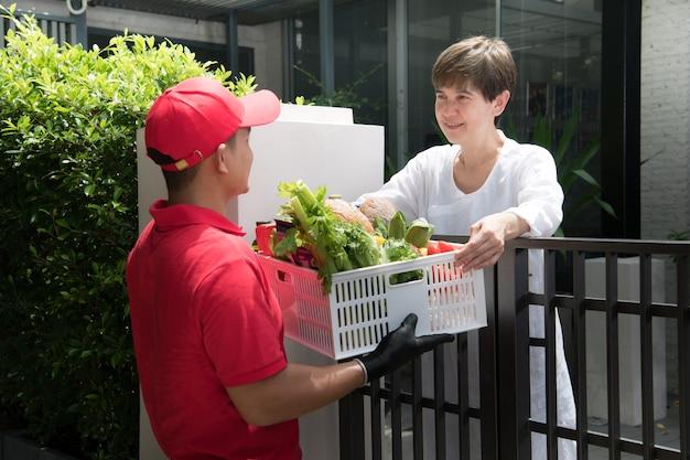 Livreur asiatique en uniforme rouge livrant des épiceries fort de nourriture, fruits, légumes et boissons à la femme destinataire à la maison