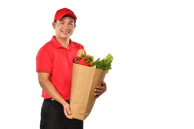 Livreur asiatique en uniforme rouge porter sac d'épicerie dans les mains isolé sur fond blanc