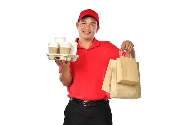 Livreur asiatique en uniforme rouge porter des sacs de nourriture et de boisson dans les mains isolés sur fond blanc