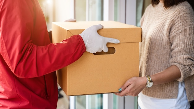 Un livreur asiatique en uniforme rouge remet un colis à une cliente devant la maison. un facteur et un service de livraison express livrent des colis pendant la pandémie de covid19.