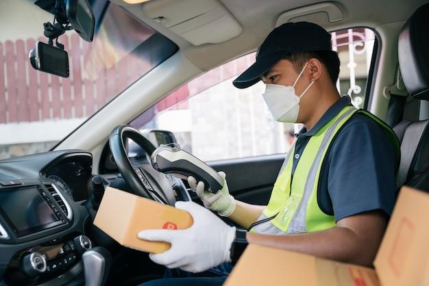 Livreur asiatique utilisant un lecteur de carte de crédit. dans la voiture avec des colis à l'extérieur de l'entrepôt. livraison