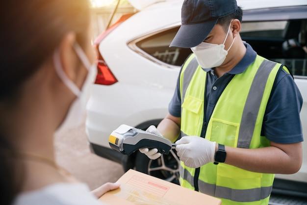Livreur asiatique utilisant un lecteur de carte de crédit tout en livrant des produits aux clients à domicile, destination de livraison.