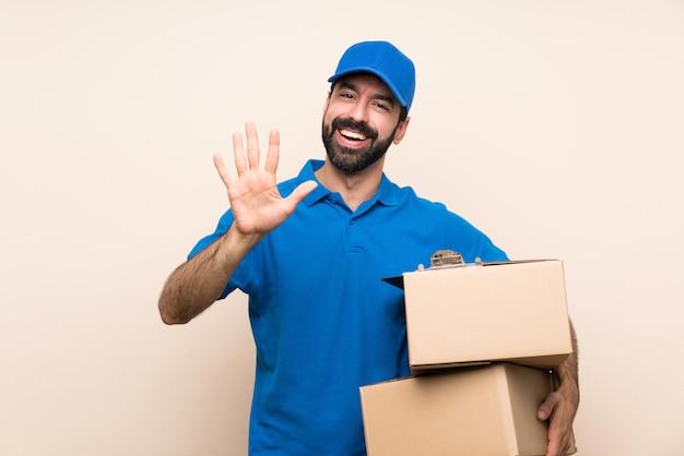 Livreur avec barbe sur mur isolé comptant cinq avec les doigts