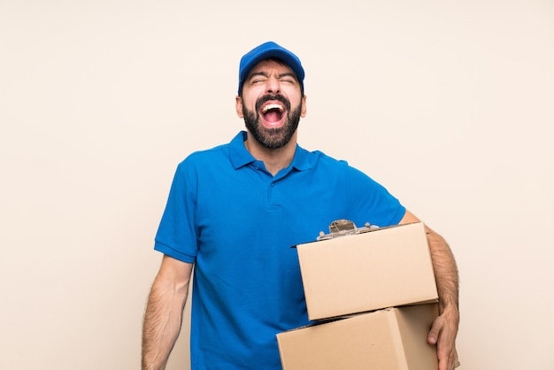 Livreur avec barbe sur mur isolé criant à l'avant avec la bouche grande ouverte