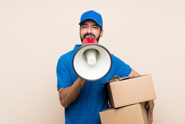 Livreur avec barbe sur mur isolé criant à travers un mégaphone
