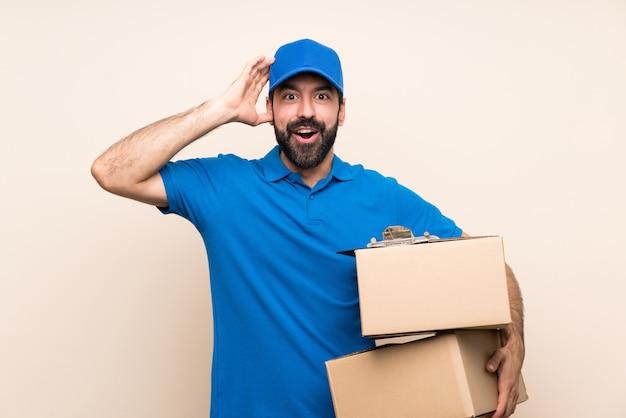Livreur avec barbe sur un mur isolé avec une expression de surprise
