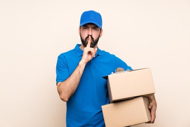 Livreur avec barbe sur un mur isolé montrant un geste du silence mettant un doigt dans la bouche