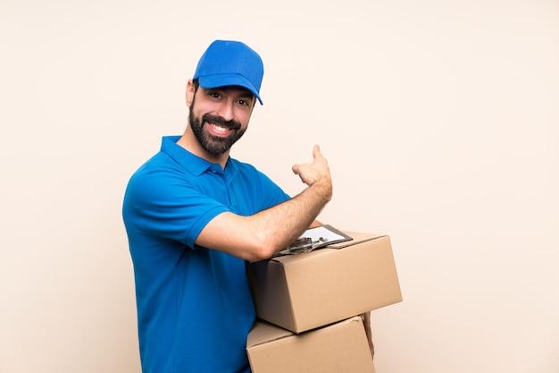 Livreur avec barbe sur mur isolé pointant vers l'arrière