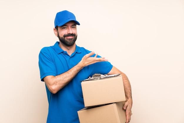 Livreur avec barbe sur mur isolé présentant une idée tout en regardant souriant