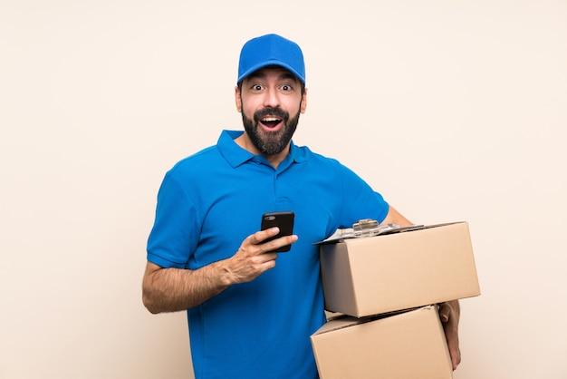 Livreur avec barbe sur mur isolé surpris et envoyant un message