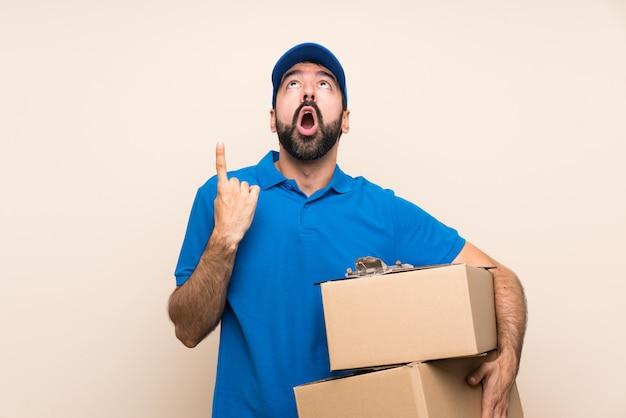 Livreur avec barbe sur mur isolé surpris et pointant vers le haut