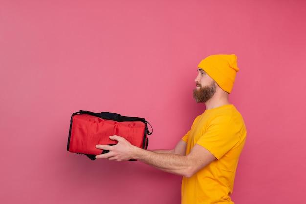 Livreur barbu européen avec boîte avec de la nourriture sur rose