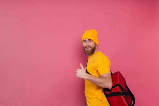 Livreur barbu européen avec boîte avec de la nourriture souriant et montrant le pouce vers le haut sur rose