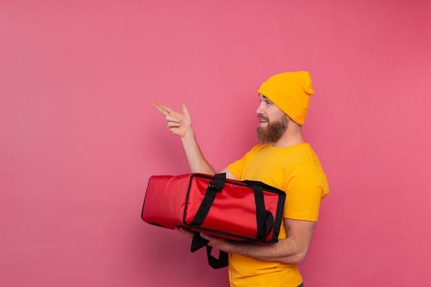 Livreur barbu européen avec fort avec de la nourriture en souriant et en pointant le doigt vers la gauche sur rose