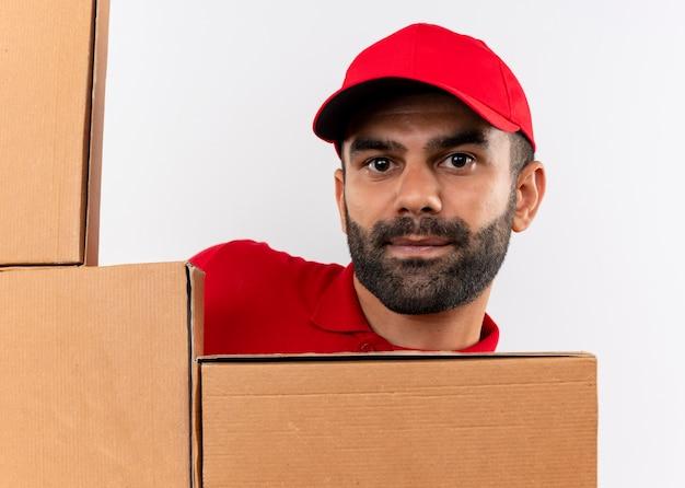 Livreur barbu en uniforme rouge et cap avec des boîtes en carton furtivement debout sur un mur blanc