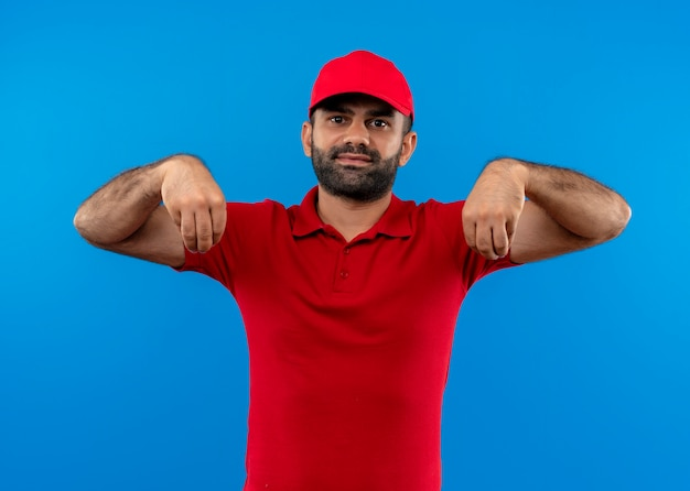 Livreur barbu en uniforme rouge et cap gesticulant avec la main à la confiance, concept de langage corporel debout sur le mur bleu