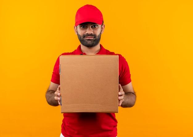 Livreur barbu en uniforme rouge et cap holding box package avec expression sérieuse confiante debout sur un mur orange