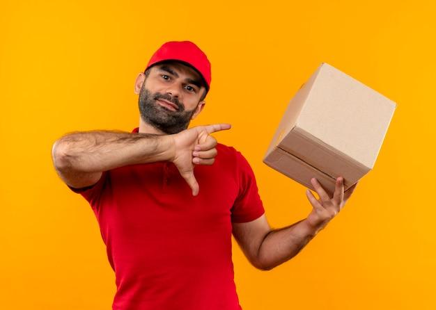 Livreur barbu en uniforme rouge et cap holding box package montrant les pouces vers le bas debout sur le mur orange