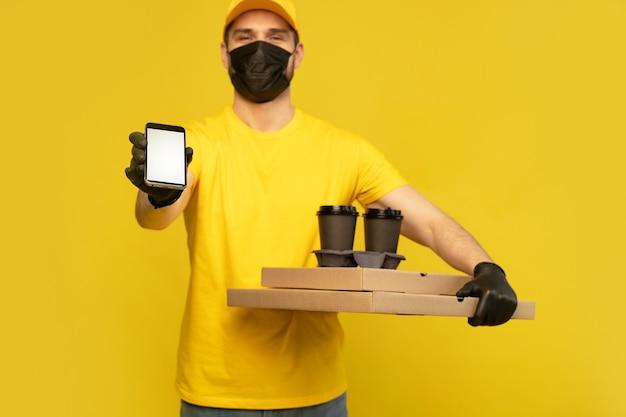 Livreur en bonnet jaune, uniforme de tshirt, masque, gants isolés. guy tenir une tasse de café à emporter