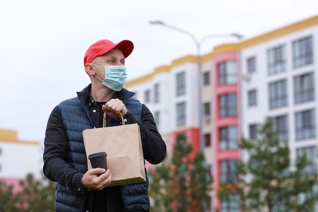 Livreur en bonnet rouge, masque médical pour le visage tenir un sac en papier à emporter et boire dans un gobelet jetable