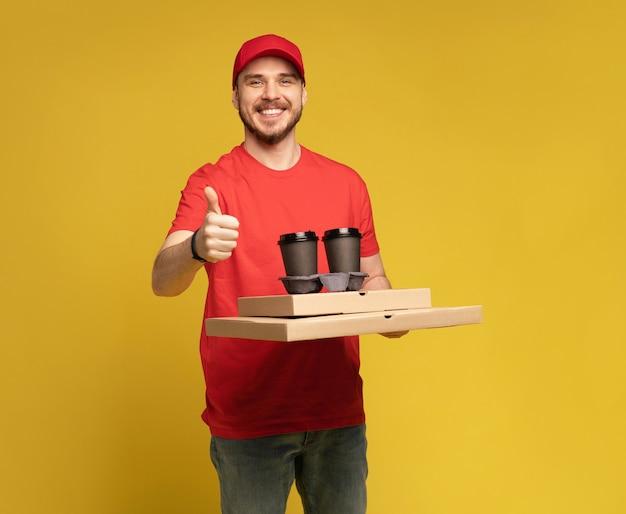 Livreur en bonnet rouge, uniforme de t-shirt isolé sur mur jaune