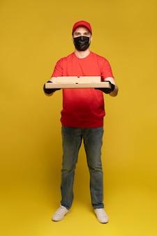 Livreur en bonnet rouge, uniforme de t-shirt, masque de protection et gants isolés sur mur jaune