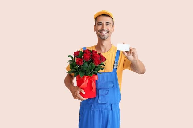 Livreur avec bouquet de fleurs et carte de visite sur la couleur
