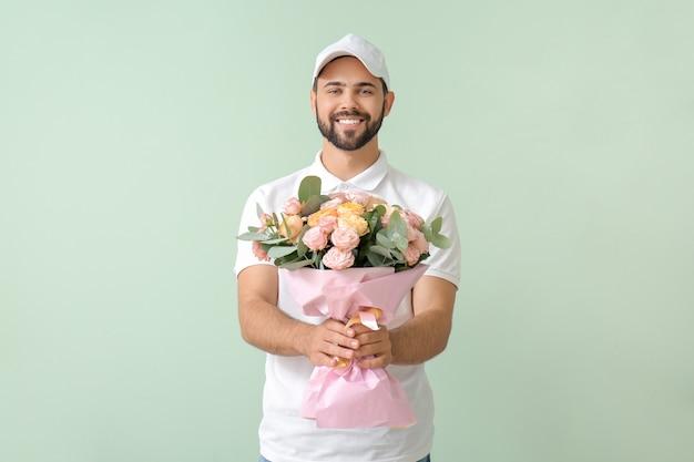 Livreur avec bouquet de fleurs sur la couleur