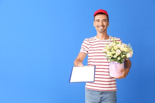 Livreur avec bouquet de fleurs et presse-papiers sur la couleur