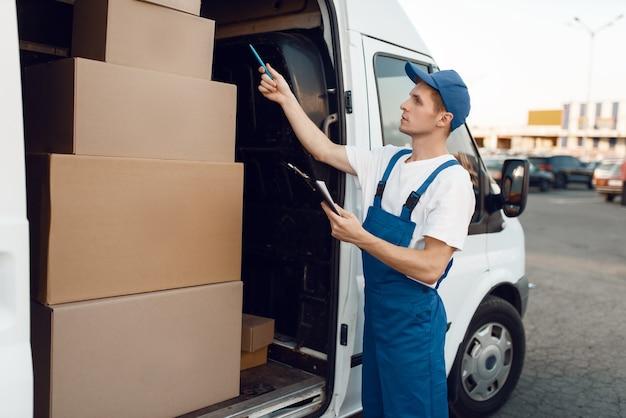 Livreur en cases à cocher uniformes dans la voiture, service de livraison. homme debout à des colis en carton dans un véhicule, un homme livrer, un courrier ou un travail d'expédition