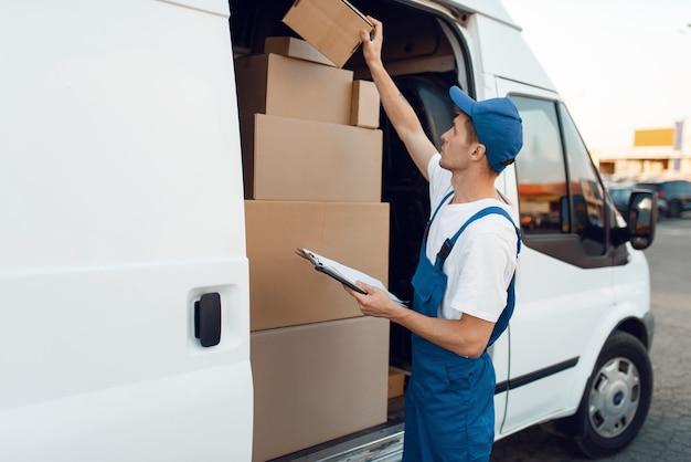 Livreur en cases à cocher uniformes dans la voiture, service de livraison. homme, debout, à, emballages carton, dans, véhicule, homme, livrer