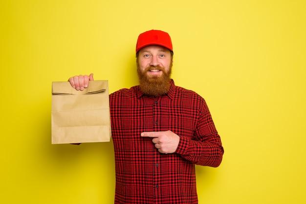 Le livreur avec chapeau et barbe a une expression heureuse