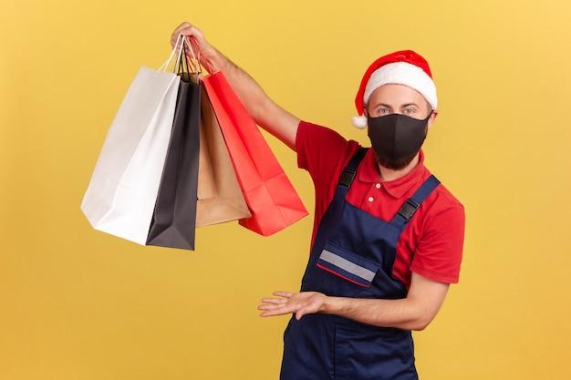 Livreur en chapeau de père noël et masque de protection noir montrant des sacs à provisions