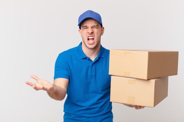 Un livreur de colis a l'air en colère, agacé et frustré de crier wtf ou qu'est-ce qui ne va pas avec vous