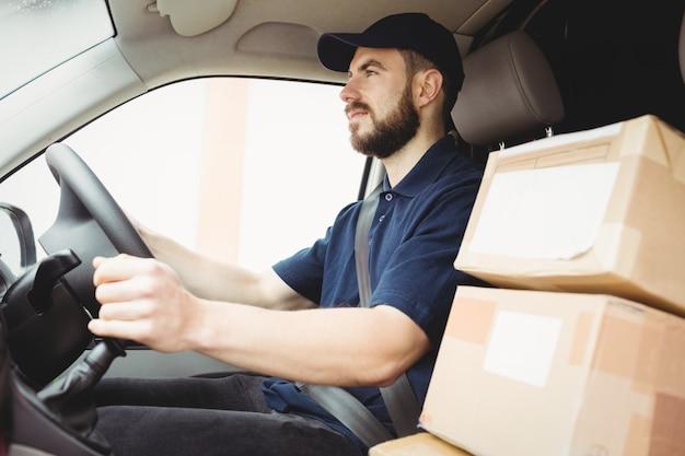 Livreur conduisant sa fourgonnette avec des colis sur le siège avant