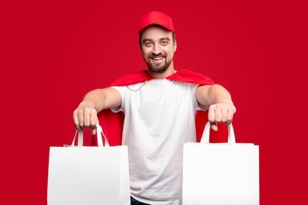 Livreur en costume de super-héros avec des sacs en papier