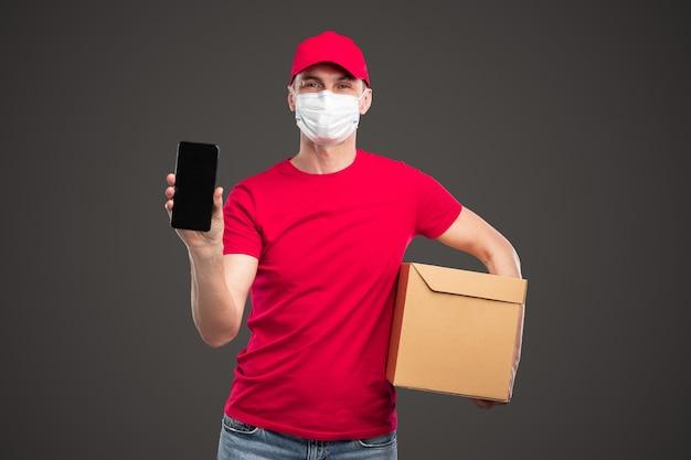 Livreur dans une boîte de transport de masque médical et montrant un smartphone avec écran noir tout en faisant la publicité d'une application de service logistique sur fond gris