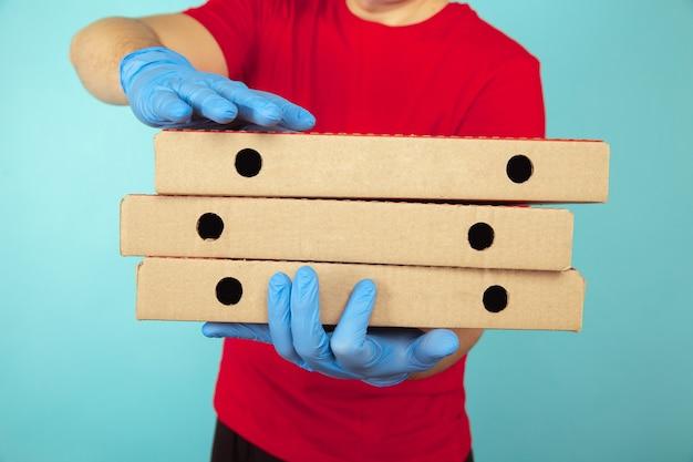 Livreur dans les vêtements rouges avec trois boîtes de pizza.