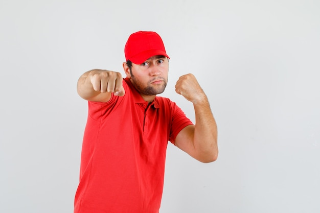 Livreur debout dans la pose de boxeur en t-shirt rouge