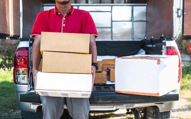Livreur debout et tenant de nombreuses boîtes à colis à son ramassage.