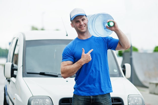 Livreur en face de fourgon offrant des bouteilles d'eau