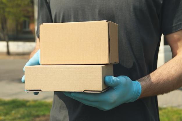 Livreur en gants détient des boîtes vierges, espace pour le texte