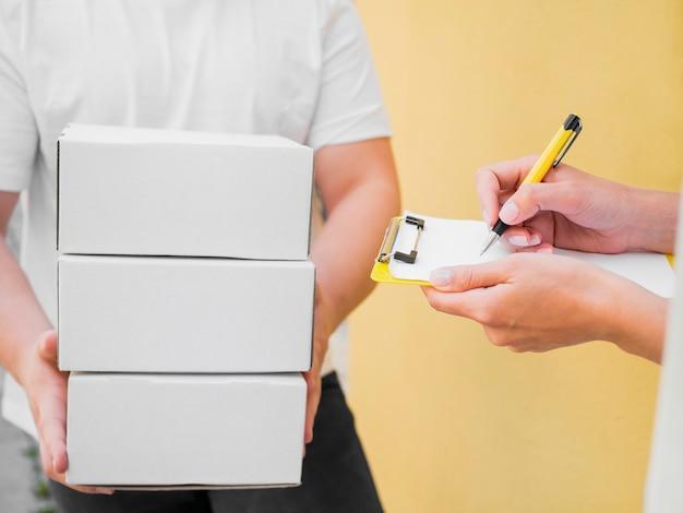 Livreur de gros plan avec des boîtes