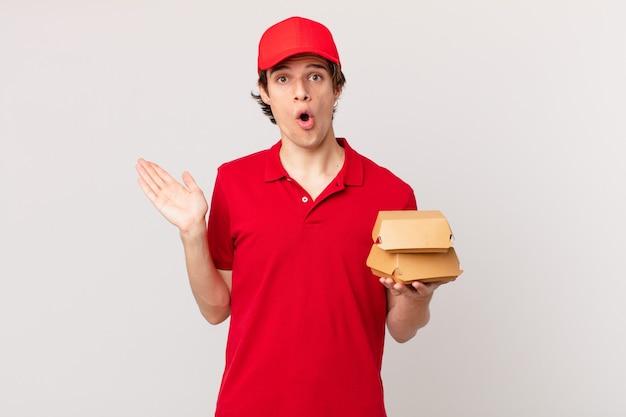 Un livreur de hamburgers a l'air surpris et choqué, la mâchoire baissée tenant un objet