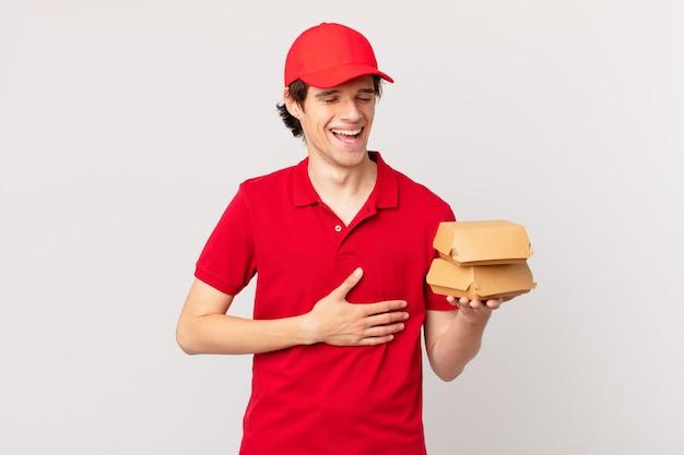 Livreur de hamburgers riant aux éclats d'une blague hilarante