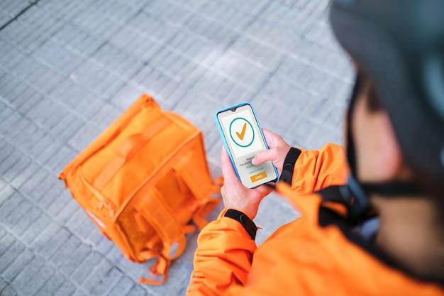 Livreur latin utilisant une application de livraison à domicile mobile