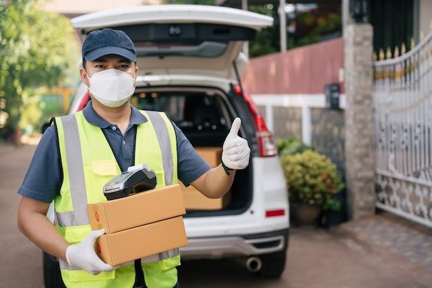 Un livreur lève le pouce et porte des masques pour empêcher la propagation du coronavirus ou du covid-19