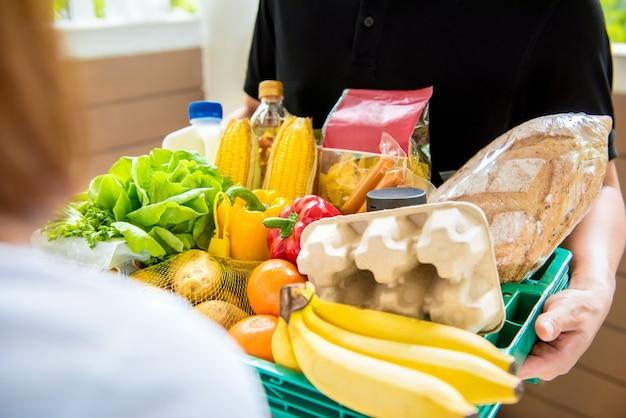 Livreur livrant la nourriture au client à la maison