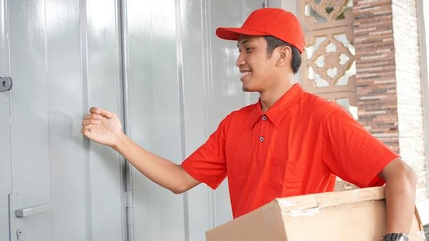 Le livreur livre la boîte devant la maison du client